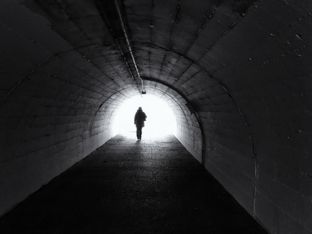 Woman goes from us to the light in the tunnel.  At the end of the tunnel you can see a bright light. A woman is dressed in winter clothes. Black and White.