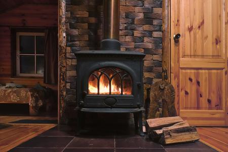 Fragment de l'intérieur d'une maison de campagne. La fournaise est chauffée. Il y a du bois près du poêle. Il fait noir devant la fenêtre. Banque d'images - 93649230