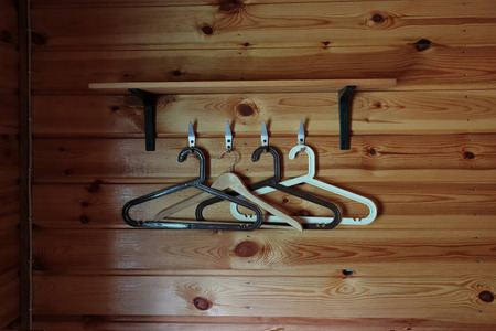 Four clothes hangers on the background of a wooden wall. The wall is made of unpainted boards. Фото со стока