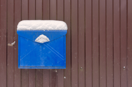 A blue metal mailbox on a brown fence. On the mailbox is a layer of snow. Background. Structure. Фото со стока