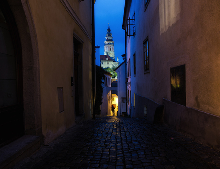 A narrow street in the old town of Cesky Krumlov in the evening. In the background, the tower of Krumlov Castle is visible. In the distance one can see the silhouette of a man with an umbrella.