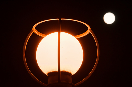 At night, a spherical street lamp from frosted glass shines. In the background, one can see the luminous circle of the full moon. The lantern is protected by a metal construction. Background. Фото со стока
