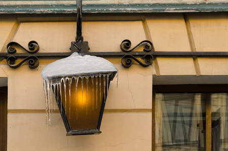 A few icicles hang from a street lamp. The lamp in the lamp is on. In the background, the wall of the building is visible. Background.