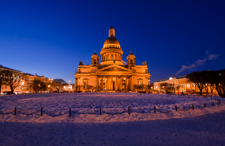 View of St. Isaacs Cathedral in St. Petersburg Russia on a winter evening. In the foreground there is a snow-covered flowerbed of the park. Sight. Stockfoto