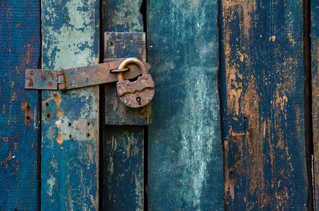 A fragment of the old blue gate is blue. The gate is locked on a rusty padlock. Background. Texture.