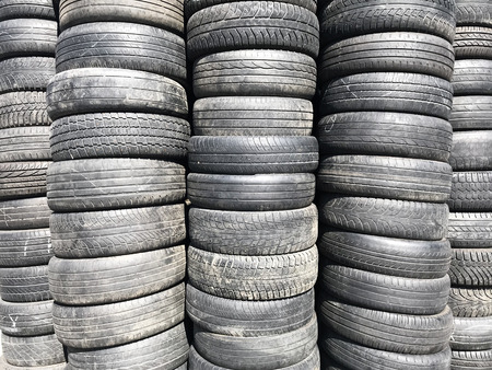 Many old tires are stacked. The tire tread is badly worn. Texture. Background.
