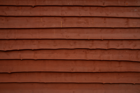 The wall of a rural house without a window. The wall is lined with horizontal lapped boards. The color of the wall is brown. Texture. Background.
