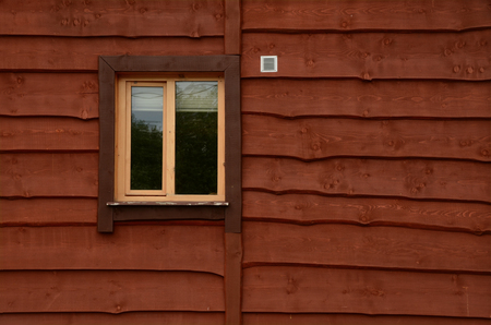 A wall of a rural house with a window. The wall is lined with horizontal lapped boards. The color of the wall is brown. Texture. Background. Stockfoto