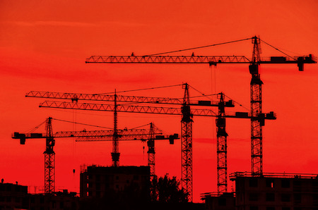Silhouettes of several construction cranes against the background of the evening red sky. There are buildings under construction underneath. Background.