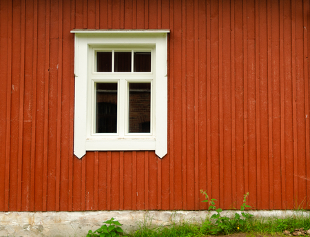 The wooden wall of the Scandinavian traditional house. The wall is painted brown. There is a window in the white frame. In the lower part you can see the foundation and grass. Background. Texture.