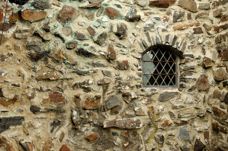 An old stone fortress wall with a small window. The texture of the natural stone is visible on the wall. The window has a grille. Background. Texture.
