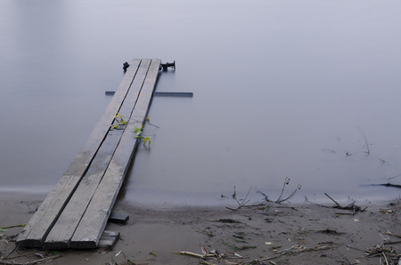 Old wooden pier on the pond. Smooth surface of water. On the ground and the berth lie fallen branches with leaves. Background.