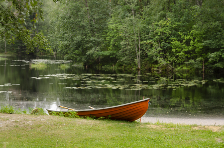 An orange boat with oars is on the shore of a forest lake. In the background there is a dense forest. Background.