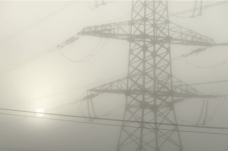 A tower supporting a high-voltage electrical line in dense fog. Through the fog visible solar circle. Background. Black and white.