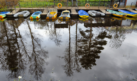 Several colorful boats at the pier on the canal. Autumn day. In the foreground - a reflection of trees in the water. Background. Stockfoto