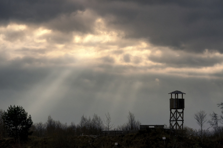The suns rays make their way through the dark clouds. On the surface of the earth are visible silhouettes of the observation tower and trees. Autumn evening. Background.