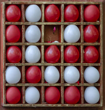 Attraction for bursting balls in a wooden grid. There are several red and white balls. One ball blown away. He was pierced by a dart. Background. Texture.