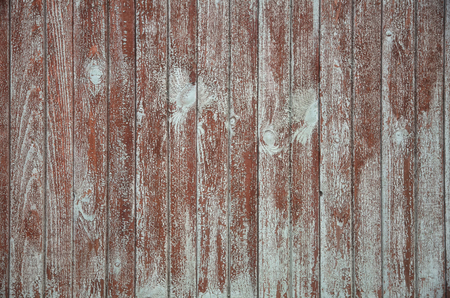 The fence of the old boards. Blue paint was peeling off. The boards have a wood texture and old red paint. Background. Texture. Stockfoto