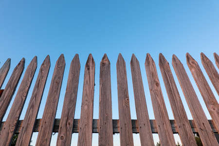 A look from below at an unpainted wooden fence made of pointed slats. The wooden elements are covered with cracks and burrs. The blue sky is visible in the background.