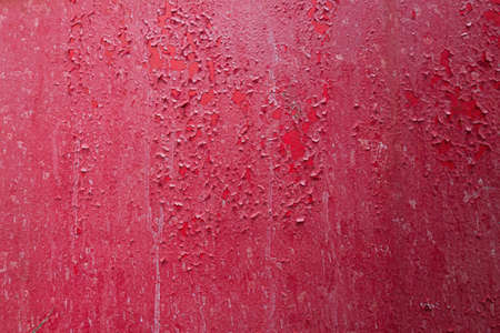 Metal sheet covered with red paint. Old paint has swollen and partially flared. The previous layer is visible. Background. Texture.