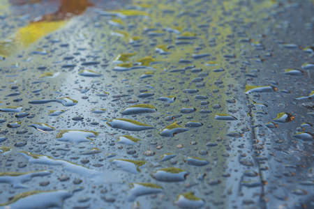 View from an angle to a surface covered with black plastic wrap. After rain, there are water droplets of various shapes. Background. Texture.