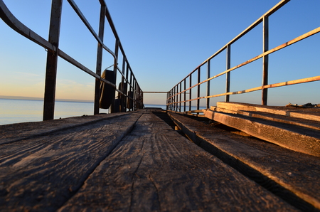 The old pier in the Volga River, lit by sun at sunset, surrounded by water and clear sky