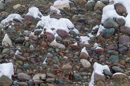 Multicolored stones under the snow Imagens