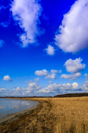 the silence of the world: shore of a small lake in the steppe on a background of blue sky with clouds Stock Photo
