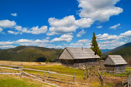 rural development: Mountain landscape with wooden house in the spring sunny day Stock Photo