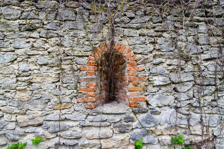 loophole: Loophole overgrown with lianas in  stone wall . Ancient fortress. Concept of peace. Stock Photo