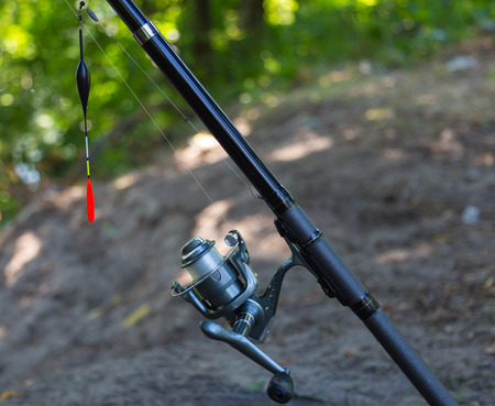 damping: Fishing rod with inertialess reel and  float close-up.