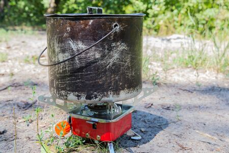 gas stove: Small camping gas stove and  large blackened pot closeup on nature