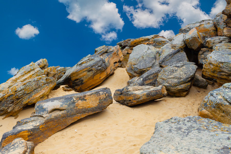 large rocks: Stone desert on  blue sky and white clouds background. Old large rocks, yellow sand.