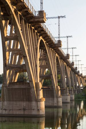 monolithic: Old curved monolithic reinforced concrete railway bridge over  river Dnieper  in  Dnipropetrovsk city. Architectural monument. Ukraine.