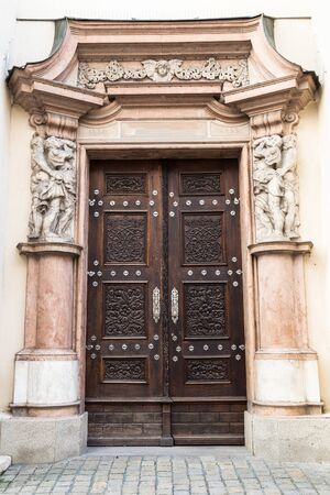old building facade: old wooden door with carved  and stone ornament on the facade of the building.