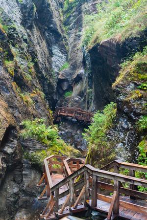 kaprun: A wooden bridge along a vertical cliff over the abyss. Austria, Kaprun Stock Photo