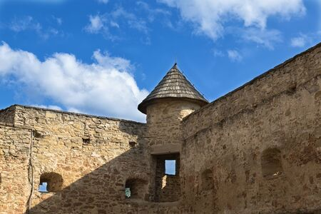 loopholes: Ancient defensive fortification with loopholes and  round tower on  background of clouds and blue sky. Castle in Stara Lubovna. Slovakia.