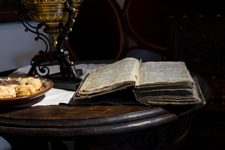 rarity: Still life with antique open book on a wooden round table. Dark photo.