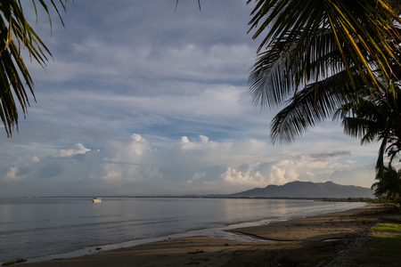 inclined: Palm trees on the beach on background the ocean and beautiful white clouds. White boat on the water. New Town Beach. Viti Levu, Fiji.