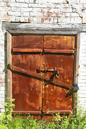 door bolt: Old iron rusty door with  bolt on an ancient brick wall - gated entrance to the basement