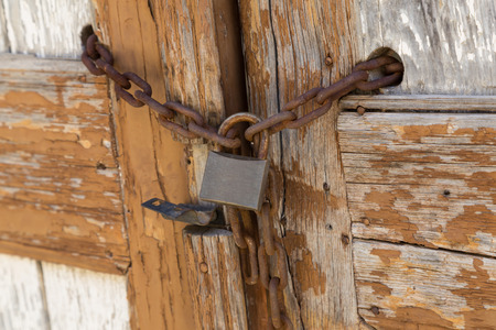 Old wooden door with  padlock, locked on the chain - fragment closeup