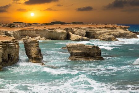 fantastic seascape - turquoise sea with waves and rocks on the background of orange sunset. Cliffs at water.  Mediterranean coast near Paphos, Cyprus Stock Photo