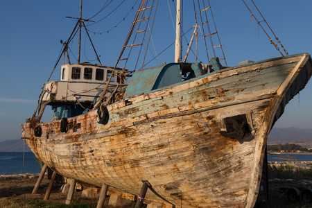 old abandoned schooner on the beach against blue sky