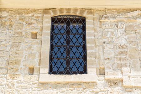 ventana de madera con celosía de hierro en la pared de piedra antigua