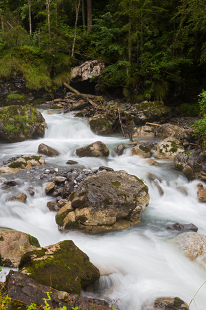 Fast mountain river  flowing among mossy stones and boulders in green forest. Stock Photo