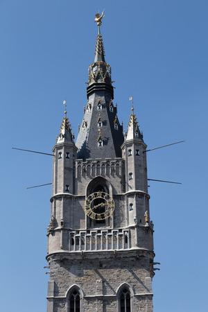 belfort: Ancient Bell Tower - watchtower - Ghent Belfort (Belfry) - top close-up on blue sky background Stock Photo