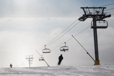 chair on the lift: Skiers on ski slope, chair lift in the fog. Strbske Pleso. High Tatra Mountains. Slovakia