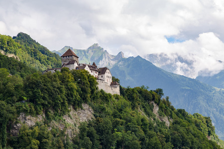Fairy Vaduz castle, Liechtenstein against the background of majestic mountains and clouds -  prince residence  Stock Photo