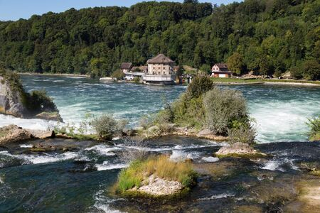 Waterfall on the river Rhine, Schaffhausen, Switzerland. The Rhine Falls is the largest waterfall in Europe in the summer day against the blue sky