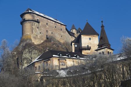 nosferatu: Famous Orava Castle ( Oravsky hrad ) on background of blue sky. Bottom view. Orava Podzámok. National Monument of Culture of Slovakia. Travel destination for vacations . Stock Photo